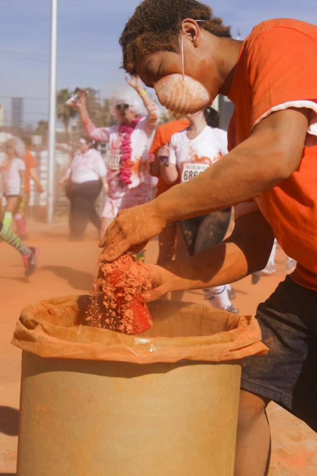 A volunteer fills up a bottle with orange powder at 5K Color Run, Saturday, Feb. 16, 2013.