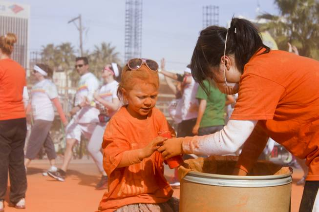 Makenzie, left, covered in orange powder, helps volunteers fill up bottles at the 5K Color Run, Saturday, Feb. 16, 2013.