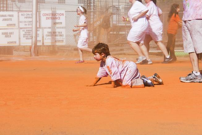 Eli, center, crawls through the orange stage of the 5K Color Run, Saturday, Feb. 16, 2013.