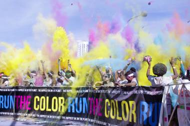 Packets of colored powder fly through the air at the color extravaganza finish line at the 5K Color Run, Saturday, Feb. 16, 2013, in downtown Las Vegas.