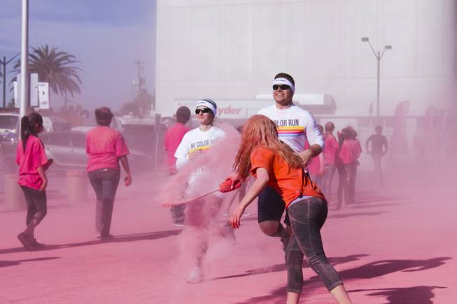A volunteer hits a couple with pink powder as they pass the pink stage of the 5K Color Run, Saturday, Feb. 16, 2013.