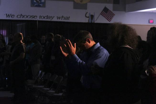 An attendee raises his hands in prayer during the Grace City Church service, Sunday, Feb. 17, 2013. The new Las Vegas church rents out the Jack Schofield Middle School auditorium as a temporary venue to hold their Sunday service.