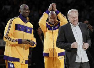 In this Oct. 26, 2010 file photo, Los Angeles Laker owner Jerry Buss, right, walks out onto the court during the NBA championship ring ceremony as Kobe Bryant, left, and Derek Fisher look on before a basketball game against the Houston Rockets in Los Angeles.