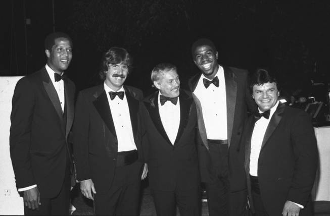 In this June 18, 1980 file photo, Jerry Buss, center, poses with players from his teams at a charity event in Beverly Hills, Calif. From left are Los Angeles Lakers' Jamaal Wilkes, Los Angeles Kings' Charlie Simmer, Buss, Lakers' Magic Johnson and Kings' Marcel Dionne.