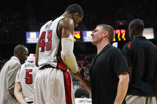 UNLV strength and conditioning coach Jason Kabo checks on forward Mike Moser's injured elbow during their game against Air Force January 12, 2013 at the Thomas & Mack.