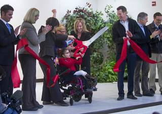 Student Madison Peck, center, helps cut a ribbon during an official opening ceremony at the new John F. Miller School, a school which serves students with disabilities and special needs, Wednesday Feb. 20, 2013. The school has been nominated for a national design award.