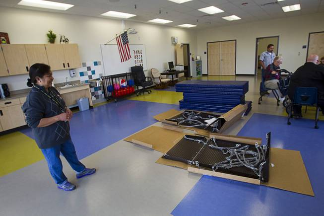Specialized teacher's assistant Susana Price looks over a wheelchair swing that is being assembled in a physical education room at the new John F. Miller School, a school which serves students with disabilities and special needs, Wednesday Feb. 20, 2013. The school has been nominated for a national design award.
