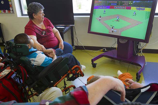 A student uses a pressure pad to play a baseball video game at the new John F. Miller School, a school which serves students with disabilities and special needs, Wednesday Feb. 20, 2013. The school has been nominated for a national design award.