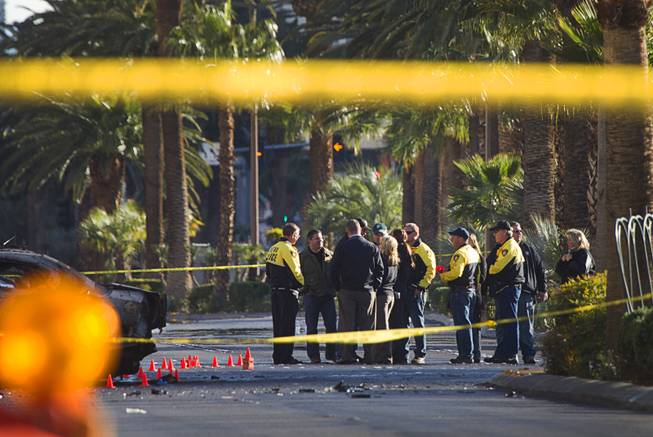 Investigators confer at the site of a shooting and multi-car accident that left three people dead and at least three injured on the Las Vegas Strip early Thursday morning, Feb. 21, 2013.