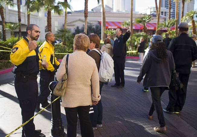 Security officers at the Flamingo give instructions to tourists near the site of a shooting and multi-car accident that left three people dead and at least three injured on the Las Vegas Strip early Thursday morning, Feb. 21, 2013. Most tourists had already heard about the shooting by the afternoon but needed directions on how to navigate around the crime scene.
