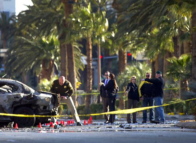 Officials investigate the site of a shooting and multi-car accident that left three people dead and at least three injured on the Las Vegas Strip early Thursday, Feb. 21, 2013.