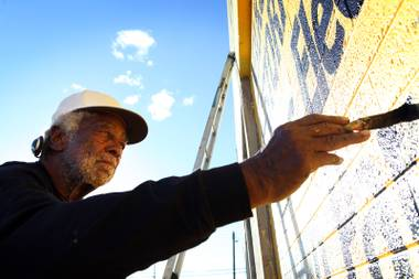 "Artist ""King"" Richard Harris works on painting the lettering for a sign at Classic V-Dubs auto repair shop on Main Street in downtown Las Vegas on Thursday, February 21, 2013."