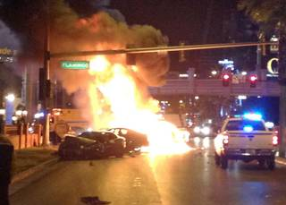 Smoke and flames billow from a burning vehicle following a shooting and multicar accident on the Las Vegas Strip early Thursday, Feb. 21, 2013.