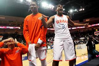 Bishop Gorman's Robert Stanley (2) jumps on a court side table to celebrate their 69-43 Division I state championship win over Centennial Friday, Feb. 22, 2013 at the Orleans.