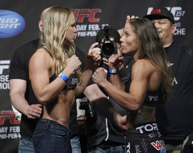 Mixed martial arts fighter UFC bantamweight champion, Ronda Rousey, left, and opponent Liz Carmouche face off at the Honda Center in Anaheim, Calif., Friday, Feb. 22, 2013. Champion Rousey will fight Liz Carmouche in the main event at UFC 157 at the Honda Center on Saturday Feb. 23, in the first women's bout in the UFC promotion's history.