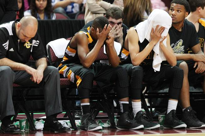 Clark players and coaches sit stunned on the bench after losing to Clark in their Class 1A basketball championship game Saturday, Feb. 23, 2013 at the Orleans Arena. After trailing almost the whole game, Desert Pines came from behind to win 59-57