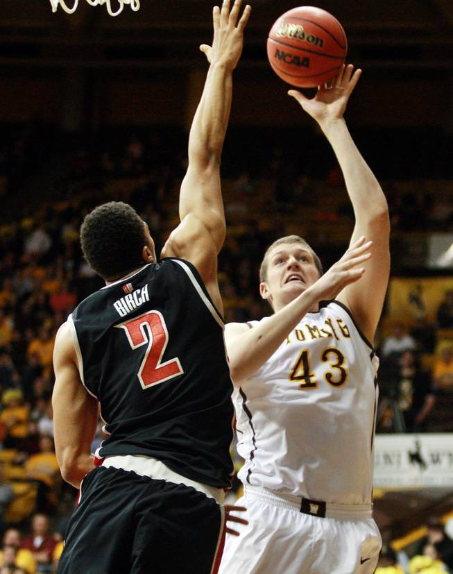 Wyoming's Matt Sellers tries to shoot over UNLV's Khem Birch during the first half of an NCAA college basketball game Saturday, Feb. 23, 2013, at the Arena-Auditorium in Laramie, Wyo. (AP Photo/Casper Star-Tribune, Alan Rogers)