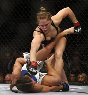 Ronda Rousey, top, punches Liz Carmouche during their UFC 157 women's bantamweight championship mixed martial arts match in Anaheim, Calif., Saturday, Feb. 23, 2013. Rousey won the first womens bout in UFC history, forcing Carmouche to tap out in the first round. (AP Photo/Jae C. Hong)