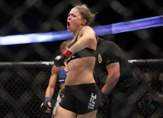 Ronda Rousey celebrates defeating Liz Carmouche after their UFC 157 women's bantamweight championship mixed martial arts match in Anaheim, Calif., Saturday, Feb. 23, 2013. Rousey won the first womens bout in UFC history, forcing Carmouche to tap out in the first round. (AP Photo/Jae C. Hong)