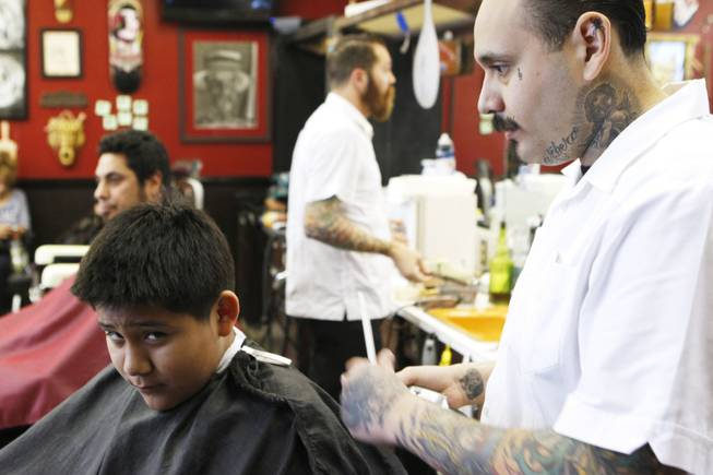 Michelangelo Estrada looks up while getting his hair cut by Martin Corona at Hi Rollers Barber Shop Saturday, Feb. 23, 2013.