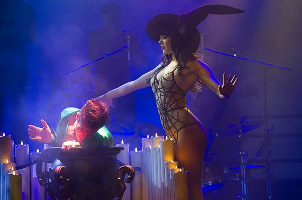 Claire Sinclair, Playboy's 2011 Playmate of the Year, pulls dancer Ryan Kelsey from her cauldron during a media preview of