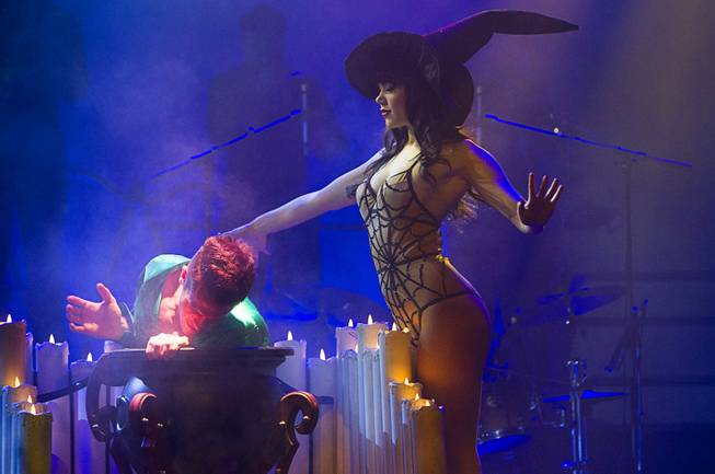 "Claire Sinclair, Playboy's 2011 Playmate of the Year, pulls dancer Ryan Kelsey from her cauldron during a media preview of ""Pin Up,"" a new show at the Stratosphere, Monday, Feb. 25, 2013. The show is scheduled to open March 2."