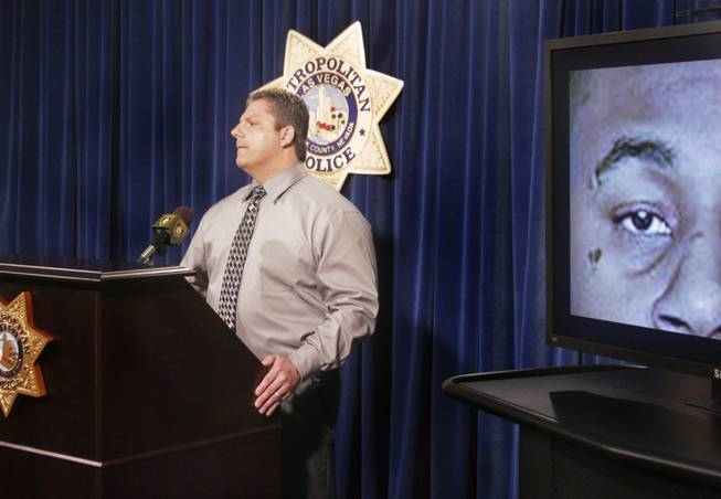 A screen shows shooting suspect Ammar Harris with a heart tattoo under his right eye while Las Vegas Metro Police Lt. Ray Steiber addresses the media with new information on the strip shooting, Monday, Feb. 25, 2013.