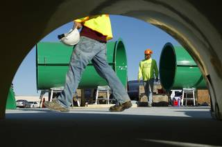 Workers assemble pieces of water slides for the new Wet 'n' Wild water park Wednesday, Feb. 27, 2013.