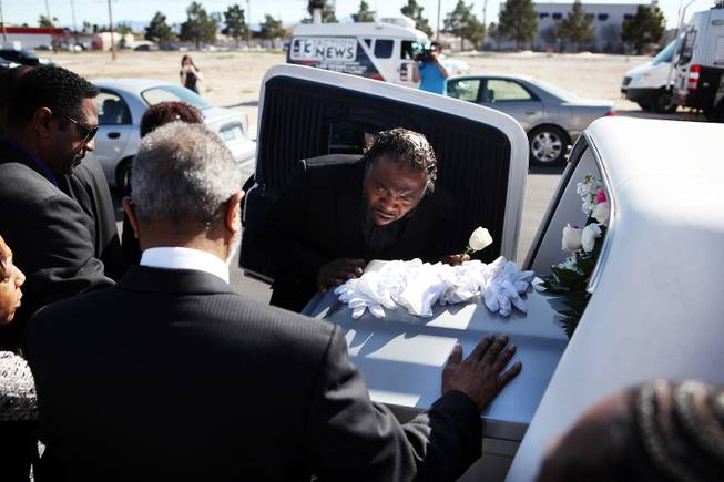 Tehran Boldon, Michael Boldon's brother, leans in to kiss his brother's coffin after the memorial service for Michael Boldon at Holy Trinity AME Church in North Las Vegas on Wednesday, Feb. 27, 2013. Boldon was killed in his cab Feb. 21, the result of a fiery crash after a shootout on the Las Vegas Strip.