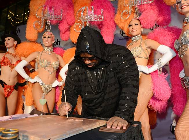"CeeLo Green is surrounded by showgirls from ""Jubilee!"" at Bally's Las Vegas during a hand-print ceremony at Planet Hollywood on Tuesday, Feb. 26, 2013."