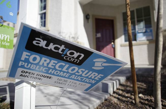 An auction sign for a foreclosed home in Las Vegas bends in the wind, Nov. 17, 2010.