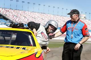 John Katsilometes gets out of his race car with some help from operations manager Corrie Matthews of the Richard Petty Driving Experience at Las Vegas Motor Speedway on Friday, March 1, 2013.