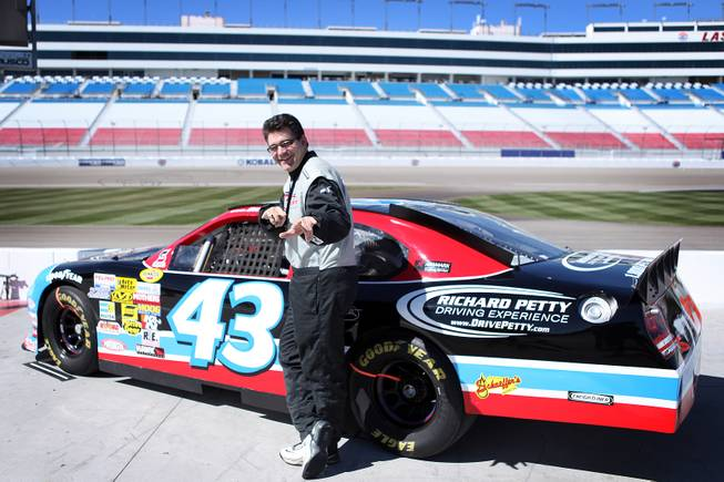 John Katsilometes poses with a race car during the Richard Petty Driving Experience at Las Vegas Motor Speedway on Friday, March 1, 2013.