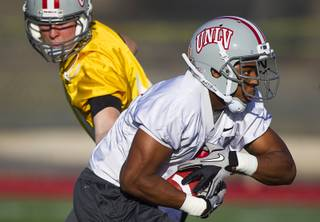Quarterback Nick Sherry hands off to running back Adonis Smith during practice at Rebel Park at UNLV Monday, March 4, 2013.