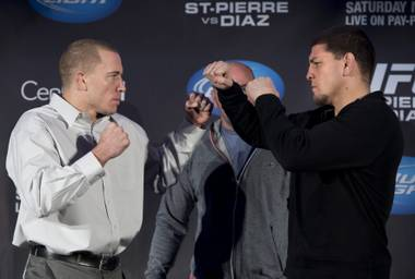 Welterweight UFC champion Georges St. Pierre, left, and Nick Diaz pose for photos as they face off during a news conference, Wednesday, Jan. 23, 2013, in Montreal. The two will fight in UFC 158 on March 16.