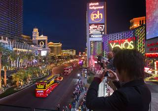 A Japanese tourist, right, takes photos during a parade of NASCAR haulers on the Las Vegas Strip Wednesday, March 6, 2013.  The NASCAR hauler parade traveled north on the Las Vegas Strip to Sahara Avenue, then on I-15 to the Las Vegas Motor Speedway.