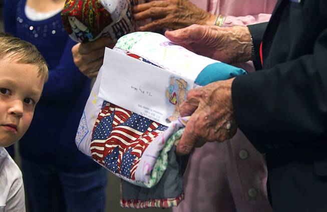 World War II veterans hold quilts as they are honored during Veterans Court in Henderson Thursday, March 7, 2013. Holden Miller, 5, helped to hand out the quilts. Moms Love Quilts, a local group that gives out quilts to military members, provided the quilts.