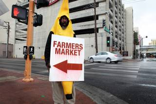Walter Thomas, Jr. promotes the downtown farmer's market during a rainy day in Las Vegas on Friday, March 8, 2013.