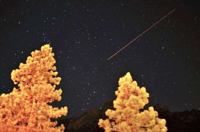 A long time exposure catches a plane flying over Mt. Charleston and the star-lit hills, below. on Saturday, Mar. 9, 2013.
