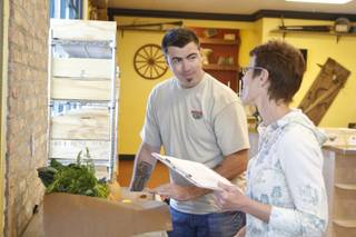 Tim McLaughlin, store manager, helps a customer at Trish & Ed's Organics, Wednesday, March 6, 2013.