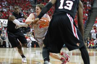 New Mexico forward Cameron Bairstow drives between San Diego State's DeShawn Stephens, left, and Winston Shepard during their Mountain West Conference Tournament game Friday, March 15, 2013 at the Thomas & Mack Center.