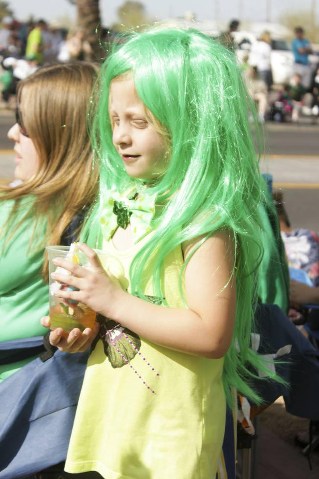 A girl wears a long green wig during the St. Patrick's Day Parade in downtown Henderson, Saturday, Mar. 16, 2013.