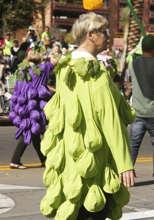A member of the Grape Expectations Nevada School of Winemaking dressed in a grape costume passes by during the St. Patrick's Day Parade in downtown Henderson, Saturday, Mar. 16, 2013.