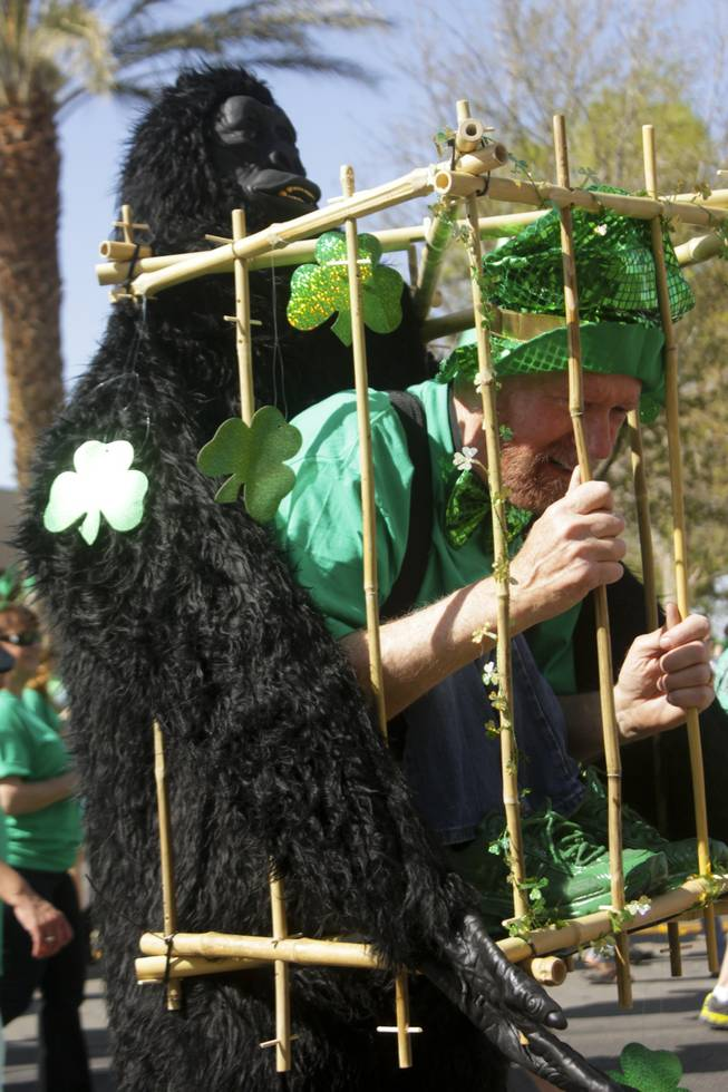 A participant in a gorilla/man-in-a-cage costume talks to onlookers during the St. Patrick's Day Parade in downtown Henderson, Saturday, Mar. 16, 2013.