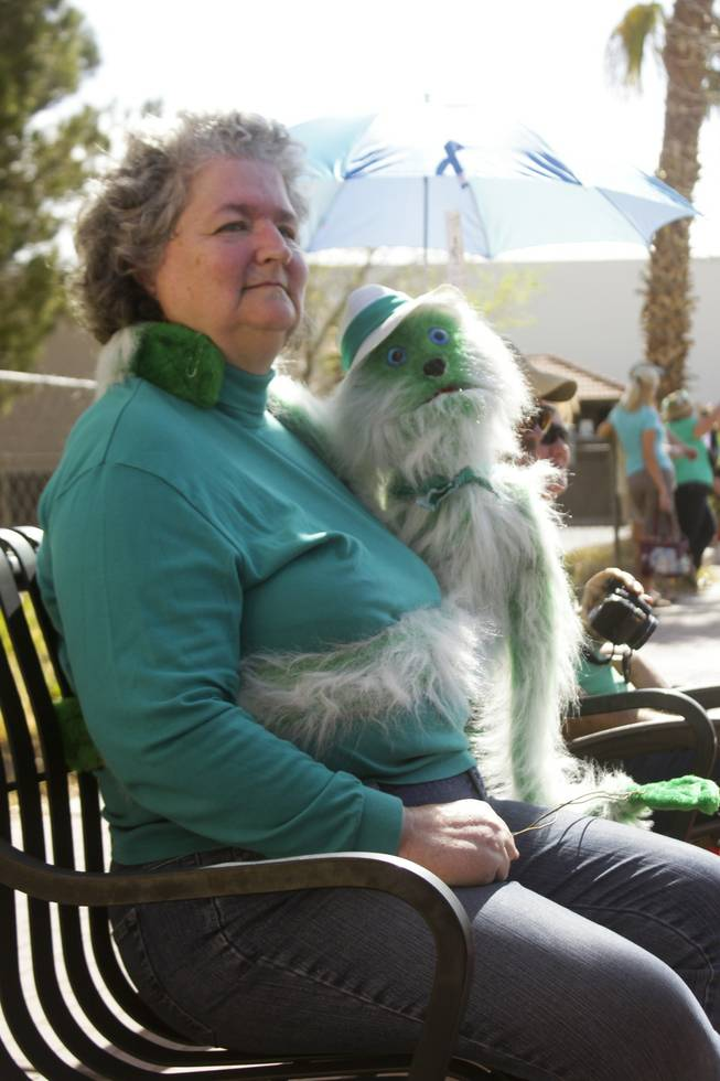 A parade goer with her green puppet watch the St. Patrick's Day Parade in downtown Henderson, Saturday, Mar. 16, 2013.