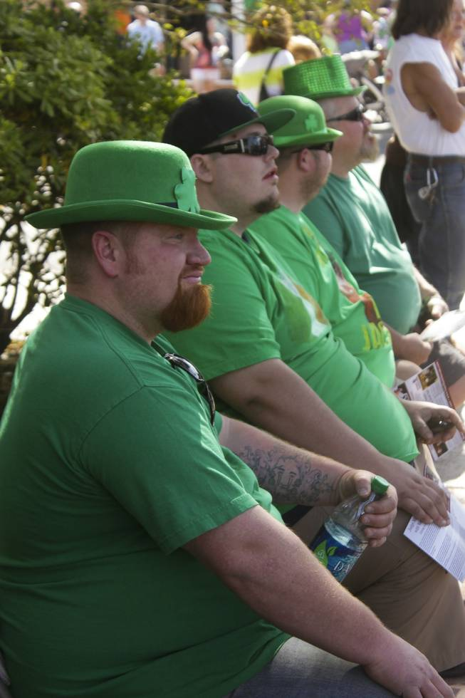Four festive men in green watch the St. Patrick's Day Parade in downtown Henderson, Saturday, Mar. 16, 2013.
