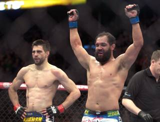 Johny Hendricks from the United States, right, celebrates following his UFC 158 welterweight fight with Carlos Condit, left, also from the United States in Montreal, Saturday, March 16, 2013.(AP Photo/The Canadian Press, Graham Hughes)