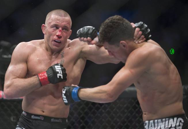 Georges St-Pierre, left, from Canada lands a blow to Nick Diaz from the United States  during their UFC 158 welterweight mixed martial arts title fight in Montreal, Saturday, March 16, 2013. (AP Photo/The Canadian Press, Graham Hughes)