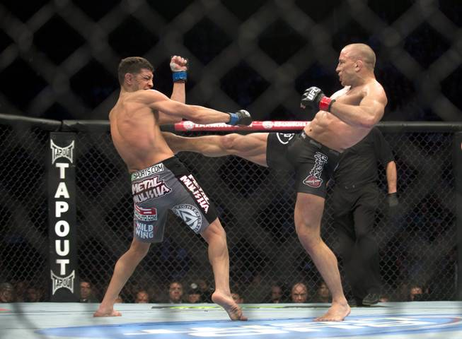 Georges St-Pierre, right, from Canada lands a kick to the body of Nick Diaz from the United States during their UFC 158 welterweight mixed martial arts title fight in Montreal, Saturday, March 16, 2013. (AP Photo/The Canadian Press, Graham Hughes)