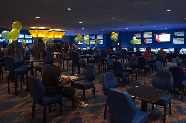 Balloons float above tables as various patrons mill about during the grand opening of the new William Hill Race & Sports Book inside the Plaza Hotel on Tuesday, Mar. 19, 2013.